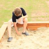 Liten unge - pojke som spelar i sand Royaltyfri Bild