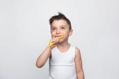 Liten unge som borstar tänder på vit Royaltyfria Bilder