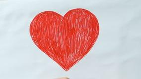 Liten unge som drar stor röd hjärta och gör ordförälskelse av kuber, vänlighet, fred arkivfilmer