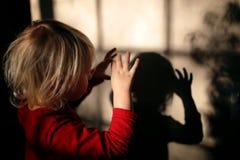 Liten unge som gör skuggadockor med fingrar på väggen av hennes hem royaltyfri foto