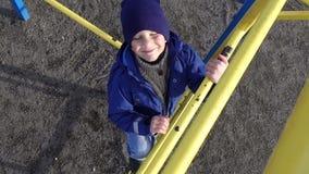 Liten unge som klättrar upp på stege i lekplats arkivfilmer