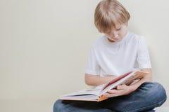 Liten unge som läser en bok Utbildning skola, fritidbegrepp Royaltyfri Bild