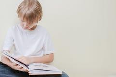 Liten unge som läser en bok Utbildning skola, fritidbegrepp Royaltyfria Bilder