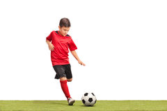 Liten unge som sparkar en fotboll Arkivbilder