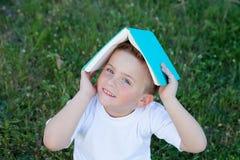 Liten unge som spelar med en bok på yttersidan Arkivfoton