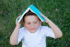 Liten unge som spelar med en bok på yttersidan Royaltyfri Bild