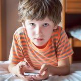 Liten unge som spelar på en smartphone Arkivbild