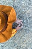 Liten unge som spelar på jordningen med smutsen och sanden arkivbild
