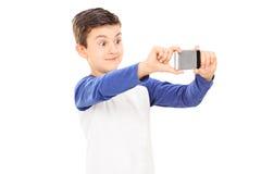 Liten unge som tar en selfie med mobiltelefonen Royaltyfria Foton
