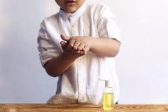 Liten unge som tvättar hans hand med antibacterialen för att stelna arkivfoto