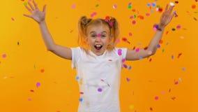 Liten upphetsad flicka som ler anseende under konfettiregn p? orange bakgrund stock video