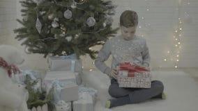 Liten upphetsad lycklig ask för gåva för gåva för pojkeöppningsjul i dekorerat rum för atmosfär för träd för nytt år festligt arkivfilmer