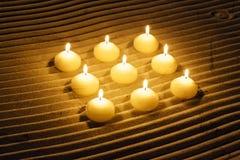 Liten uppsättning av bränningstearinljus i randig sand för ayurveda Arkivfoto