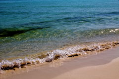 Liten våg av kristallklart vatten som kysser en sandig strand Arkivbild