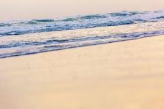 Liten våg som kommer till stranden, och glas- fluffig vit avbrottsvåg på sanden med guld- solljus för bakgrund arkivfoto