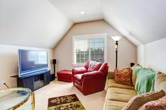 Liten vardagsrum med den röda fåtöljen och TV Arkivbild
