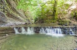 Liten vattenfall i bergskog med silkeslent skumma vatten Royaltyfri Foto