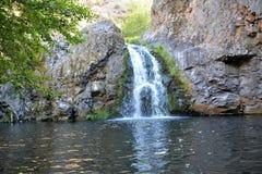 Liten vattenfall med simninghålet under Arkivbild