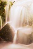 Liten vattenfall på den lilla bergströmmen, mossigt sandstenkvarter Klart kallt vatten är brådskan som hoppar ner in i liten pöl Arkivbild