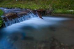 Liten vattenfall på en liten flod med lång exponering Arkivfoton