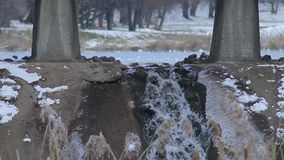 Liten vattenfall under bron på bakgrunden av sjön på vinterwather arkivfilmer