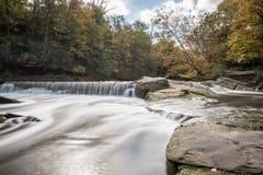 Liten vik med den silkeslena vattenfallet i höst Fotografering för Bildbyråer