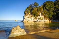 Liten vik på solnedgången i Abel Tasman National Park, Nya Zeeland Royaltyfria Bilder