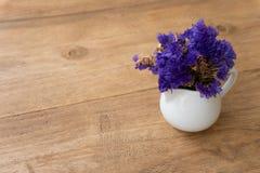 Liten violett blomma i en vit kopp på en trätabell royaltyfri foto