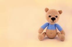 Liten virkad nallebjörn på en försiktig gul bakgrund Handgjord mjuk leksak Royaltyfri Bild