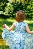 Liten virvlande runt flicka i en blå klänning i sommarträdgård Arkivfoto