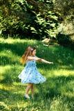 Liten virvlande runt flicka i en blå klänning i sommarträdgård Arkivbild