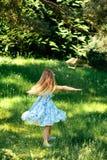 Liten virvlande runt flicka i en blå klänning i sommarträdgård Royaltyfria Foton