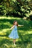 Liten virvlande runt flicka i en blå klänning i sommarträdgård Royaltyfria Bilder