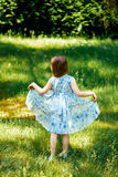Liten virvlande runt flicka i en blå klänning i sommarträdgård Royaltyfri Fotografi
