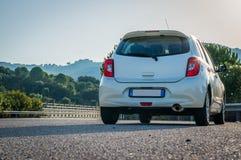 Liten vit bil med ledd optik på huvudvägen för asfaltväg Arkivbilder
