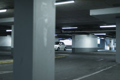 Liten vit bil som parkeras i tomt garage royaltyfria foton
