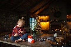 Liten vit blond flicka som sitter på en trätabell i vardagsrummet av chalet som dekoreras för julgran- och girlandintelligens royaltyfri bild