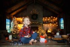 Liten vit blond flicka som sitter på en trätabell i vardagsrummet av chalet som dekoreras för julgran- och girlandintelligens royaltyfri fotografi