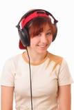 litening音乐的滑稽的女孩耳机对年轻人 库存照片
