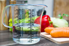 1/2 Liter/500ml/5dl Wasser in einem Messbecher auf einer Küchenarbeitsplatte mit Gemüse Lizenzfreie Stockfotos