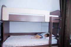 Litera en habitación del niño niña solamente que miente en cama sombra del chocolate en el interior con las paredes blancas foto de archivo