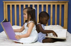 Literacy and Diversity. Two small children reading together on a bed Royalty Free Stock Images