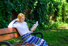 Literary critic. Lady pretty bookworm busy read book outdoors sunny day. Woman concentrated reading book in garden. Girl. Sit bench read book nature background royalty free stock image