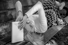 Literatura aburrida Prepárese para la rotura cansada mujer de la toma de la cara de la prueba que se relaja en libro de lectura d fotos de archivo libres de regalías