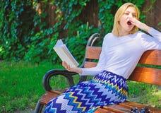Literatura aburrida Rotura rubia de bostezo de la toma de la mujer que se relaja en libro de lectura del jardín La muchacha sient imagenes de archivo
