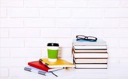 Literatura, café y cuadernos de la educación con los accesorios en lugar de trabajo cerca de la pared de ladrillo Visión superior Fotografía de archivo libre de regalías