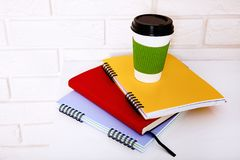 Literatura, café y cuadernos de la educación con los accesorios en lugar de trabajo cerca de la pared de ladrillo Visión superior Foto de archivo