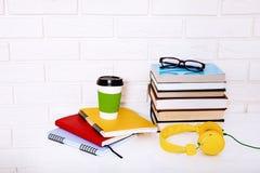 Literatura, café y cuadernos de la educación con los accesorios en lugar de trabajo cerca de la pared de ladrillo Visión superior Fotos de archivo libres de regalías