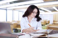 Literatura de la lectura del estudiante mientras que escribe en el libro Fotografía de archivo