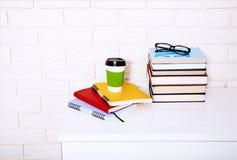 Literatura y cuadernos de la educación con los accesorios en lugar de trabajo cerca de la pared de ladrillo Visión superior y foc Fotos de archivo